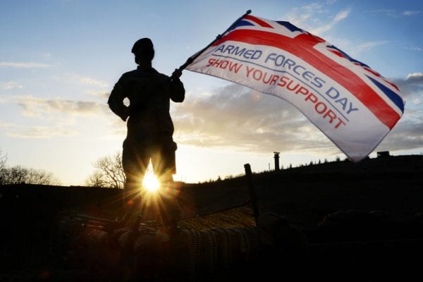 Soldier waving armed forces flag
